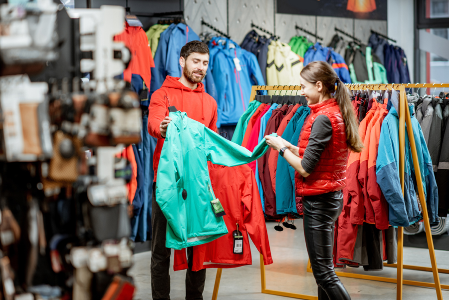 Couple choosing jacket in the sport shop